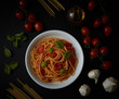 spaghetti dish with tomato sauce and basil on black background - 196523665