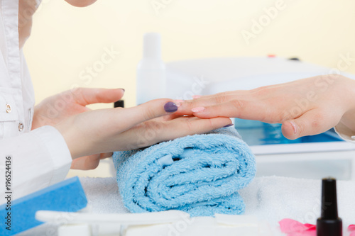 Foto op Canvas Manicure Woman hand on towel, next to manicure set