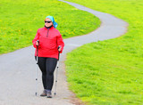 Overweight woman walking on meadows trail. Slimming and active lifestyle theme.  - 196537273
