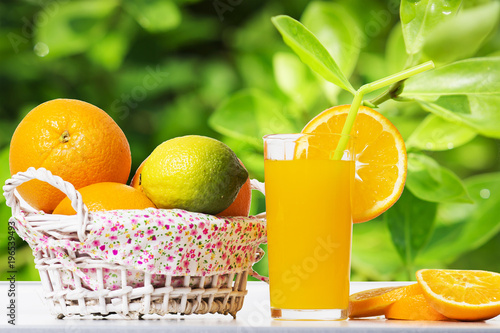 Foto op Canvas Sap Fresh orange juice and oranges in basket on table against background of green leaves of orange tree. Summer tropical citrus fruits. Orange slices and glass with juice on background of green foliage.