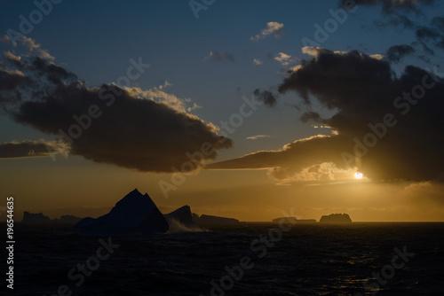 Iceberg at sunset against sun