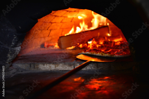 Canvas Pizzeria Preparing of a real Italian pizza in a wood-burning stove. An old and authentic restaurant background.