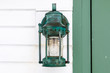 A vintage style green lantern attached to a lighthouse.
