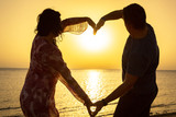 Couple maing heart shape at sunrise on the beach - 196557221