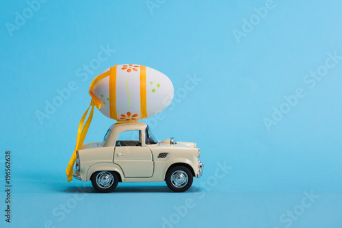Toy car carrying easter egg isolated on blue background