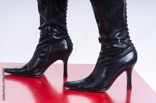 Black festish boots on red background schwarze fetischstiefel auf rotem Hintergrund - 196565884