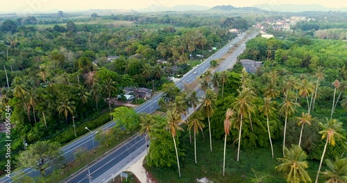 Sticker Aerial drone view of road on tropical island during sunset