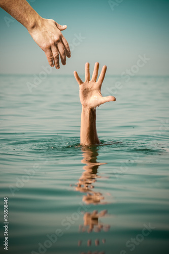 hand of help for drowning man life saving in sea water