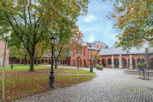 Foto op Aluminium Herfst a walking pave behind Oslo Church through foliage trees and red brick building undr blue sky