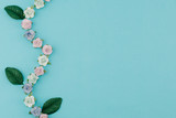 Blue tone paper flowers and green leaves on pastel blue background with copy space - 196600634