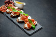 italian food with olives and prosciutto bruschettas on stone board - 196602258