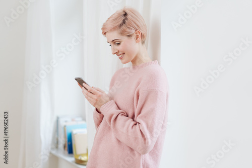 Smiling happy young woman reading a text message