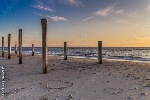 The light of golden hour at the beach with wooden piles and hearts drawings in the sand Petten, Holland, North Sea