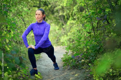 kaukaska sportowa dziewczyna w niebieskiej koszuli i czarne legginsy sportowe wykonuje rozgrzewkę z nogami przed joggingiem na kolorowym zielonym lesie bac
