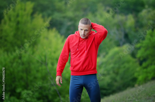 Wall mural  runner in red jacket with a hood and black sport leggins rest after jogging on a colorful green forest