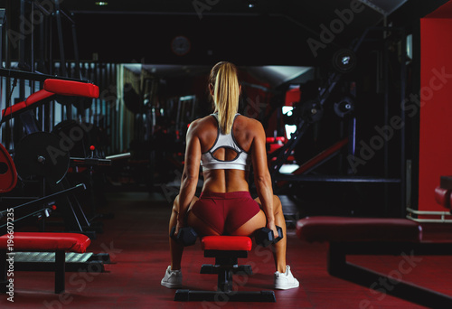Wall mural Young woman exercising with weight in the gym.