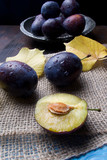 Purple fresh raw plums with autumn leaves