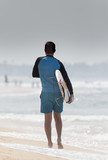 Man with surfboard walking to water - 196610609