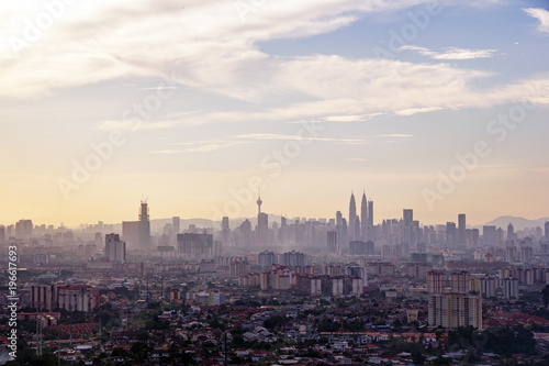 Fotobehang Kuala Lumpur Kuala LumpurÕs iconic skyline and skyscrapers in late afternoon with golden colour and high level cirrus clouds in the blue sky