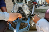 Asian people are repair or maintenance adapted engine for local boat