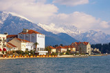 Seaside town at the foot of the snowy mountains. Montenegro, Bay of Kotor, view of embankment of Tivat city and snow-capped peaks of Lovcen mountain