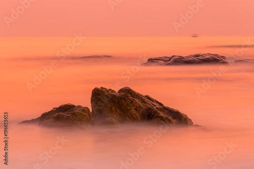 Deurstickers Koraal long exposure of the sunrise over the sea and rocks