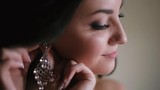 The side close-up portrait of the young attractive happy bride with natural make-up putting the earrings. Morning of the bride. - 196674669