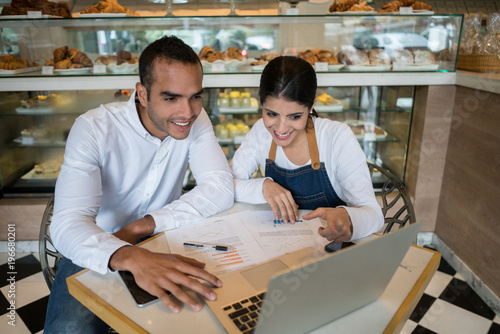 Business owner of a bakery and female administrator sitting checking the bookkeeping on the laptop both smiling