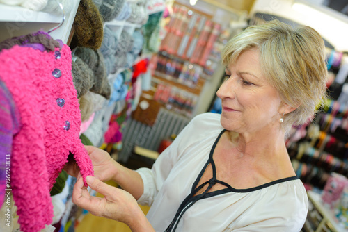 Lady looking at child's knitted jacket
