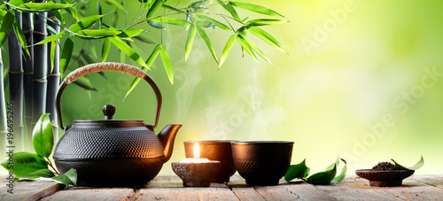 Fototapeta Black Iron Asian Teapot and Cups With Green Tea Leaves