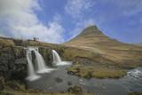 Lonf exposue photography of kirkjufell with kirkjufellfoss under blue cloudy sky