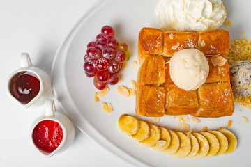 Desserts, Toast topped with vanilla ice cream, served with whipping cream, grape, banana, bean, honey and strawberry sauce on white background