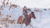 Equestrian sport - rider woman on horse galloping in snowy field - 196719423