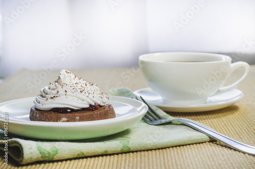 Poster A cup of tea, pieces of chocolate and a chocolate cake with egg white cream closeup