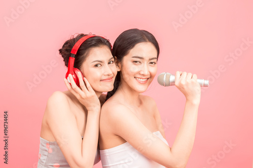 Fototapeta Happy two women singing in microphones on pink background