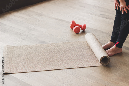 Plakat Woman makes the yoga exercise on the mat, indoors