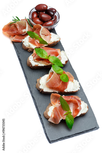 italian food with olives and prosciutto bruschettas on stone board - 196735045