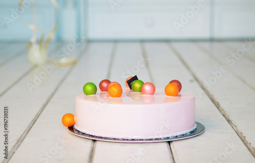 Pink mousse cake with colorful balls on a white wooden floor