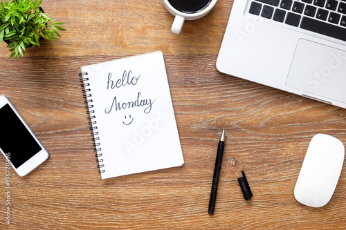 Notebook with hello Monday text on it over wood office desk table with supplies. Top view, flat lay.