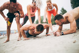 Group young attractive people having fun on beach and doing some fitness workout.