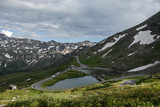 A beautiful view of the lake, the meadow and the highest surfaced mountain road in Austria - Grossglockner High Alpine Road.