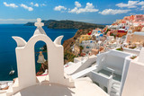 Arch with a bell, white houses and church with blue domes in Oia or Ia, island Santorini, Greece - 196798027
