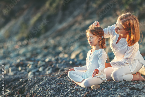 Plakat Happy family mother and child doing yoga, meditate in lotus position on beach