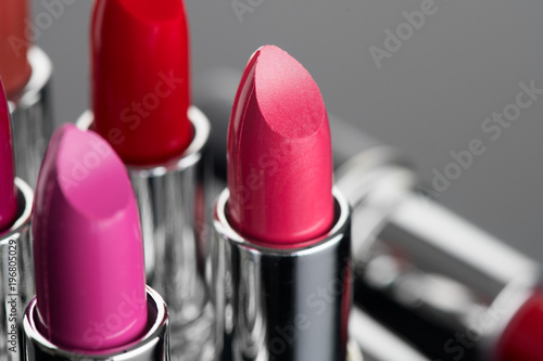 Lipstick. Professional makeup and beauty concept. Fashion pink lipsticks over black background