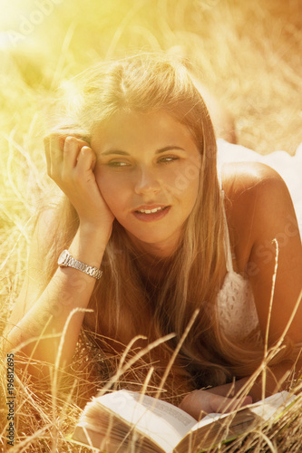 Young blonde woman lies in a golden summer field on dry grass with book.