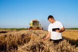 Young agronomist man standing in a golden wheat field with tablet and checking quality while combine harvester working behind. - 196834492