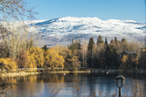 Panoramic view of Puigcerda lake on winter, with snowy peak mountain, yellow trees reflected on the frozen lake - 196835024