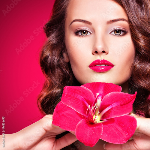 beautiful adult girl with bright red lips and flower near the face