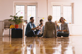 Modern cheerful young people working together on the office floor and raising togetherness. - 196836832