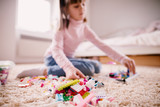 Close up focus view of big group plastic toys on the carpet while little toddler girl playing behind. - 196839666